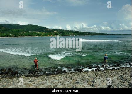 Fishermen on surf beach, Lombok, Indonesia - Stock Image