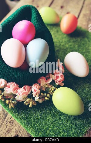 A beautiful and colorful close-up of easter eggs in a wool basket with flowers over green grass and a amazing bokeh of wooden tables as background - Stock Image