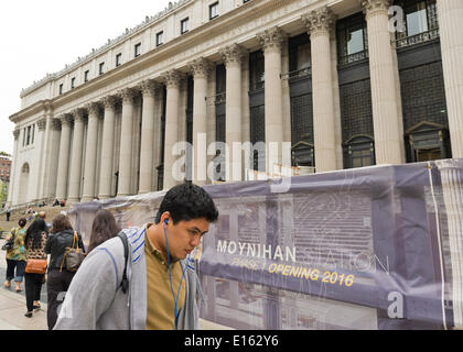 Manhattan, New York, U.S. - May 21, 2014 - Pedestrian walks past construction sign for new West End Concourse on 8th Avenue at the James A Farley Post Office, which is the future home of Moynihan Station in midtown Manhattan. The Empire State Development project is scheduled for a Phase 1 Opening 2016. - Stock Image