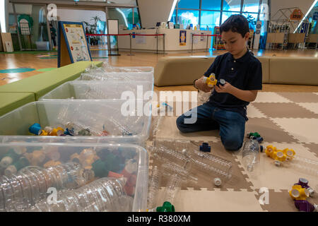 A child plays with a plastic bottle based constuction set at a children's play centre in South Korea. - Stock Image