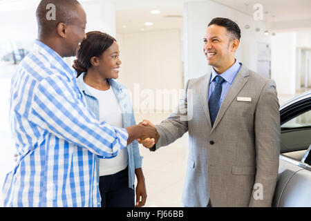 middle aged salesman handshaking with happy African couple - Stock Image