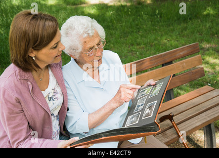 Senior woman sitting on park bench with granddaughter, looking at old photograph album - Stock Image
