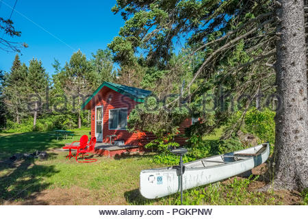 Canoe with electric motor is in front of a cabin located a short walk from Lake Superior, near Grand Marais, Minnesota, USA. - Stock Image