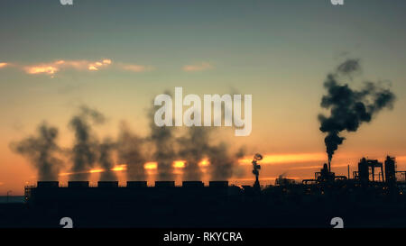 Silhouetted cooling towers and steam from a geothermal power plant in Calipatria in California at sunset. - Stock Image