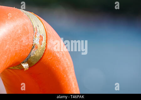 orange life buoy in the pool. orange lifebuoy on a background of water. Life buoy, for the emergency case. Summer vacation concept. Orange Safety - Stock Image