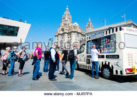 Pier Head in Liverpool, on the banks of the River Mersey, people queue to buy an Ice Cream to col down on the unusually hot day, in front of the Liver Building, on a sunny Bank Holiday Weekend, Liverpool, England UK Europe - Stock Image