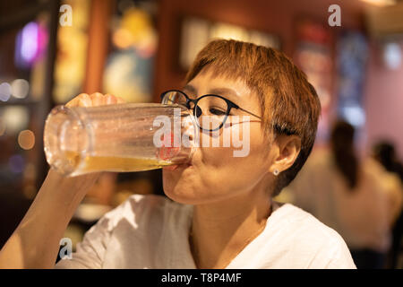 Mature Taiwanese woman of Chinese ethnicity drinking beer in a warm, cozy restaurant - Stock Image