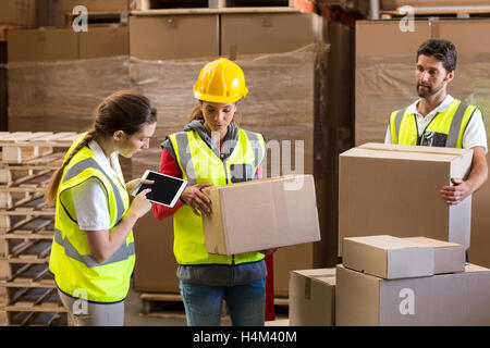 Manager noting on digital tablet while workers carrying cardboard boxes - Stock Image