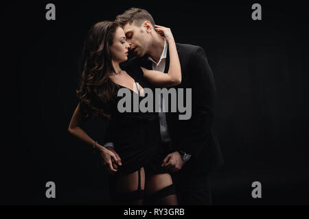 beautiful woman passionately embracing handsome man in formal wear isolated on black - Stock Image