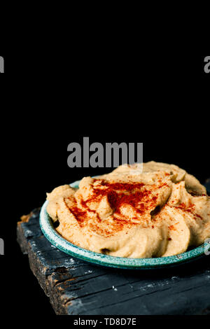 a homemade hummus seasoned with paprika served in a green ceramic plate, on a dark gray rustic wooden table against a black background with some blank - Stock Image