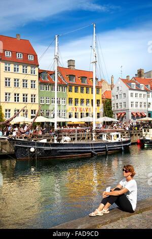 Turist relaxing at Nyhavn Canal, Copenhagen, Denmark - Stock Image