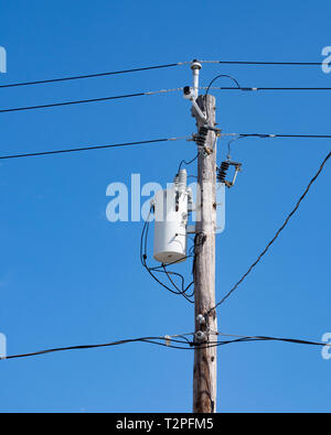 An electric transformer and transmission wires, cable TV and telephone wires attached to an old wooden power pole with a deep blue sky background. - Stock Image