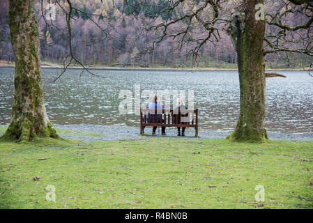 Two ladies sitting on a wooden seat relaxing by the beautiful Buttermere Lake in the English lake district of Cumbria England UK. - Stock Image