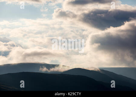 Low cloud drifting over the summit of Fairfield in the Lake District, UK. - Stock Image