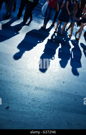 Sihouettes and shadows of people crossing the street - Stock Image