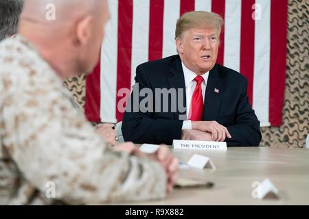 U.S. President Donald Trump meets with military leaders and takes questions from the traveling media during a surprise visit to Al Asad Air Base December 26, 2018 in Al Anbar, Iraq. The president and the first lady spent about three hours on Boxing Day at Al Asad, located in western Iraq, their first trip to visit troops overseas since taking office. - Stock Image