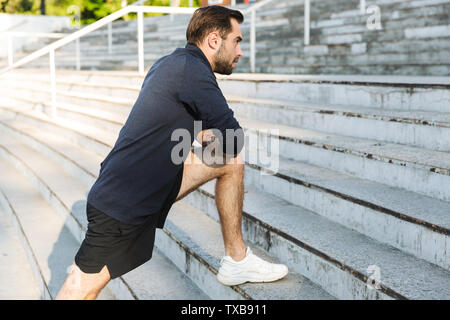 Image of a handsome young strong sports man posing outdoors at the nature park location make stretching exercises. - Stock Image