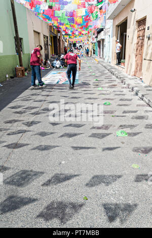 Papel picado banners cast a shadow on the street as residents create giant floral carpets made from colored sawdust and decorated with flowers during the 8th Night Celebration marking the end of the Feast of St Michael in the central Mexican town of Uriangato, Guanajuato. Every year the town decorates 5km of road with religious icons in preparation for the statue of the patron saint to be paraded through the town. Uriangato became an international sensation after wowing Brussels with their floral carpet displayed at the Brussels Grand-Place during the Belgium Floral Carpet festival. - Stock Image