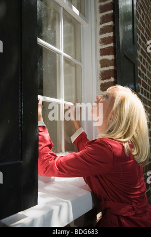 A young woman tries to open a window of a home from the outside, Charleston, South Carolina, USA - Stock Image