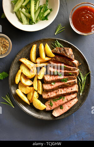 Sliced medium rare roast beef with potato wedges on plate over stone background. Top view, flat lay - Stock Image