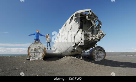 Low angle view of couple standing on airplane wreckage in remote landscape under blue sky - Stock Image