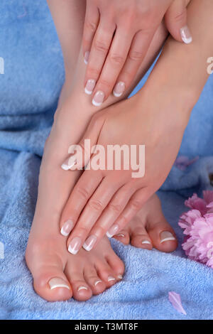Female legs with bare feet and hands with french manicure and pedicure on blue towel and decorative pink flower spa studio. Girl health care concept. - Stock Image