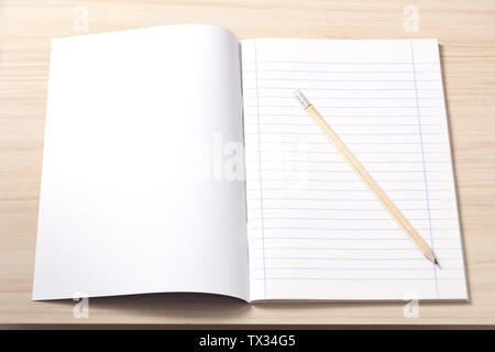 Open notebook with blank sheets and a pencil on a desk, workplace. - Stock Image