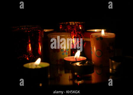 Lit candles with flames flickering in the darkness at nighttime - Stock Image