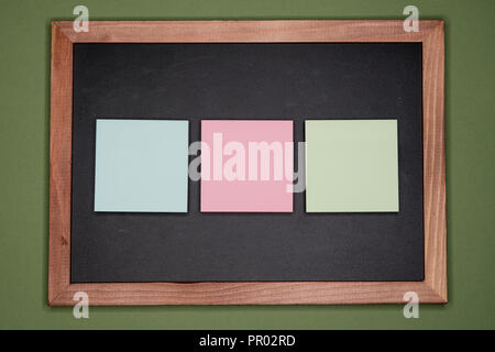 Colorful sticky notes on chalkboard on green background, blank copy space - Stock Image