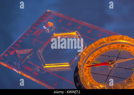 Macro-photo of compass rose face with needle. Night navigation and Outward Bound concept. - Stock Image