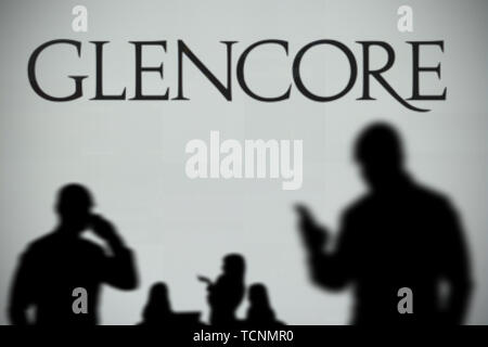 The Glencore logo is seen on an LED screen in the background while a silhouetted person uses a smartphone in the foreground (Editorial use only) - Stock Image