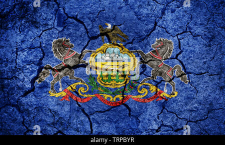 Flag of the Commonwealth of Pennsylvania on dry earth ground texture background - Stock Image