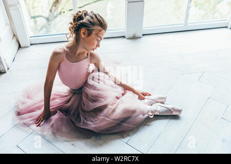 Young classical ballet dancer girl in dance class. Beautiful graceful ballerina in pink tutu skirt puts on pointe shoes near large window in white lig - Stock Image