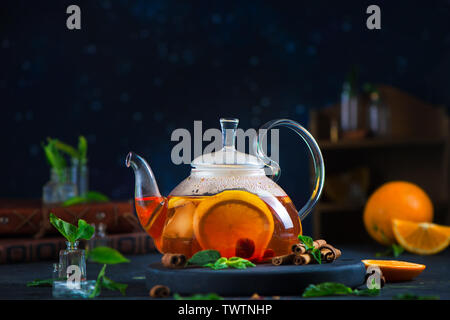 Citrus tea header with cinnamon and mint leaves in a glass teapot, dark food photography with copy space. - Stock Image