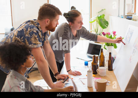 Creative designers discussing story board in office - Stock Image