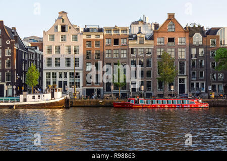 Traditional Dutch buildings on Amstel river in Amsterdam, Netherlands - Stock Image