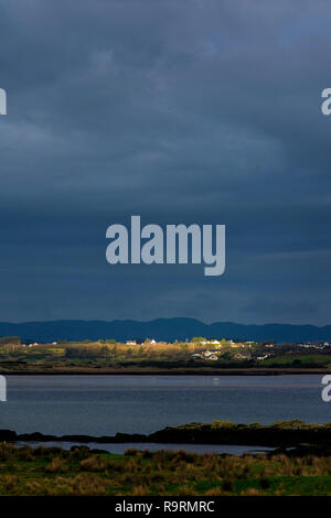 Ardara, County Donegal, Ireland. 27th December 2018. A narrow beam of sunshine highlights coastal cottages on an unseasonally warm but overcast day. Credit: Richard Wayman/Alamy Live News - Stock Image