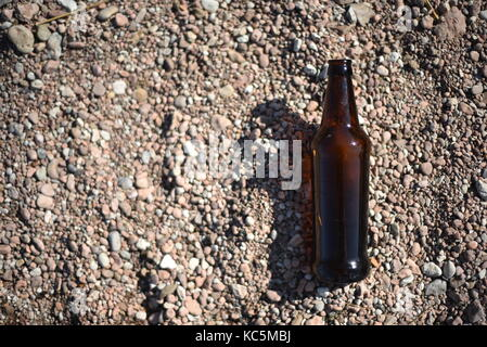 Clear unlabeled blank brown glass bottle floats in shallow water with a stones and pebbles below the surface - Stock Image