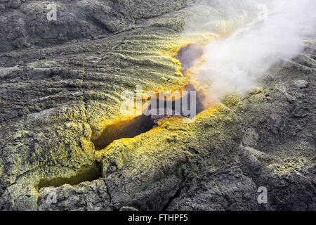 Sulfur vapor escapes from a fumarole ​which forms yellow-colored crystals around the margins of the crack inside - Stock Image