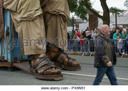 A man walks past the feet of the Giant during the Giants Spectacular parade through Liverpool city centre UK - Stock Image