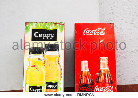 Poznan, Poland - February 7, 2019: Locked Cappy juice and Coca Cola vending machines against a wall. - Stock Image