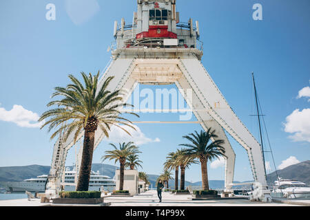 Crane in Porto Montenegro in Tivat in Montenegro. Below it a small person or tourist girl looks at the sights. - Stock Image