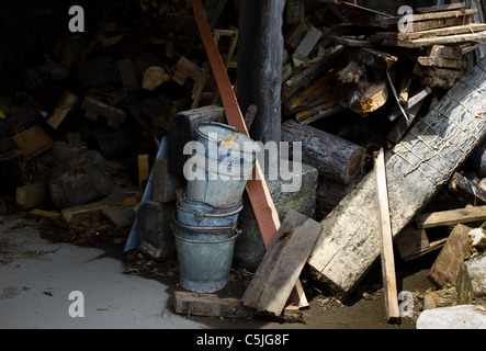 Rustic farm wood pile with stack of rusty buckets. - Stock Image