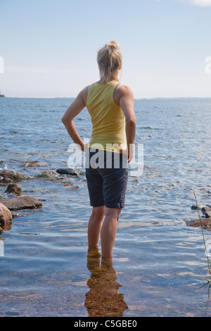 Woman standing in the water in the Archipelago of Stockholm, Sweden - Stock Image