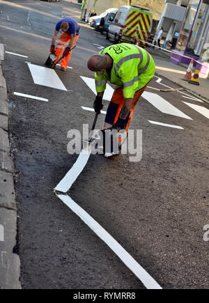 Workman applying hot white road line marking paint on zebra-stripe and pedestrian cross-walk on newly surfaced road - Stock Image