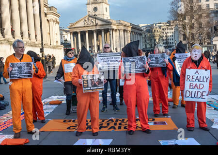 London, UK. 11th January 2019. Members of the Guantanamo Justice Campaign, London Guantanamo Campaign including a man in a Trump mask mark 17 years since the first prisoners arrived at the illegal US camp with a display of poster, photographs of the remaining detainees, readings and speeches in Trafalgar Square to highlight the abuse, torture, lack of human rights, force-feeding and indefinite detention there and call for its closure. Credit: Peter Marshall/Alamy Live News - Stock Image