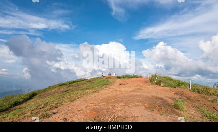Tourists on the mound and blue sky with white cloud above high mountain at viewpoint of Phu Chi Fa Forest Park in - Stock Image