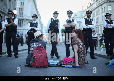 Police with Extinction Rebellion demonstrators at Oxford Circus in London. - Stock Image
