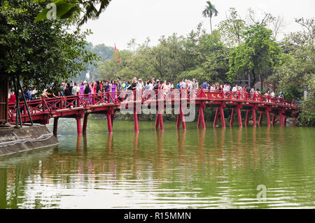 Wooden red Huc bridge to Ngoc Son Temple busy with tourists visiting Hoan Kiem lake. Hanoi, Vietnam, Asia - Stock Image