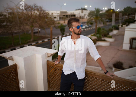 Young man stands on the balcony in white shirt and sunglasses on background of street. - Stock Image